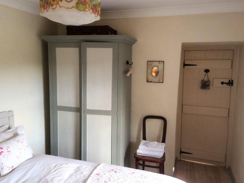 Master bed vintage linen press and light shade.