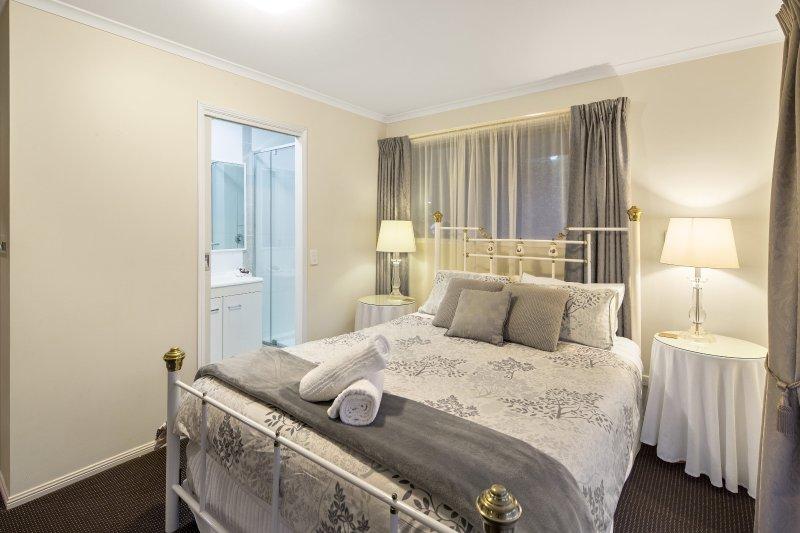 Een queen kamer met een witte, koperen bed en een kleine maar moderne badkamer