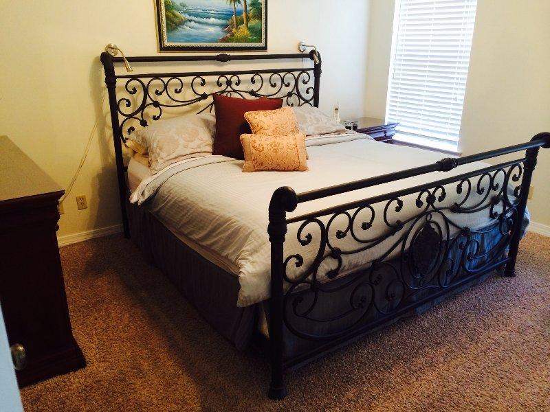 Espaçoso quarto principal com cama king size e banheiro privativo.