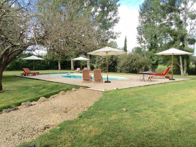 Mirando hacia la piscina y los campos más allá. Muebles de piscina de lujo y sombrillas.