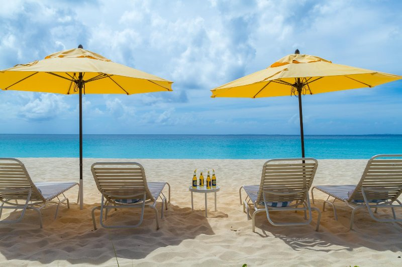Beach chairs and umbrellas set up on Meads Bay for the exclusive use of our guests