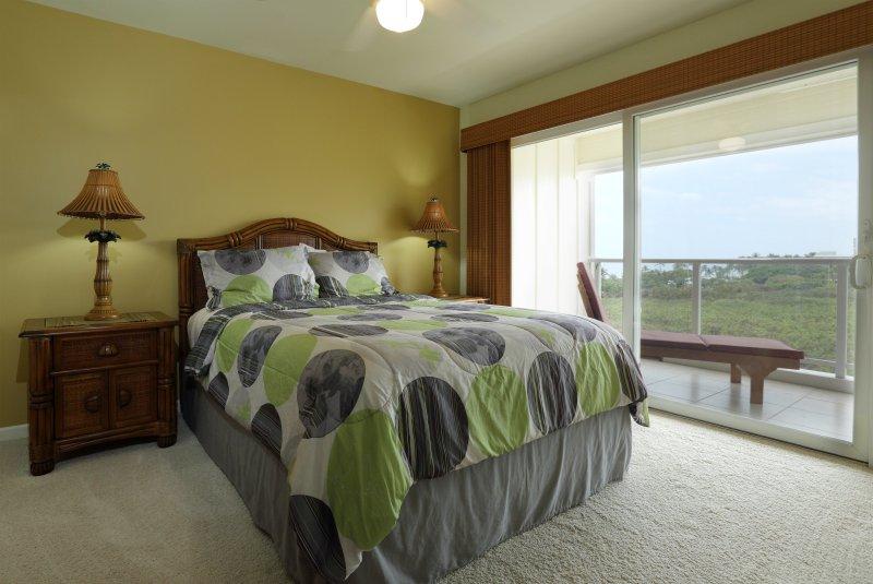 Im Obergeschoss Gast Schlafzimmer mit Doppelbett, Kommode, Kabel-TV, Lanai Zugang und unverbaubarem Meerblick.