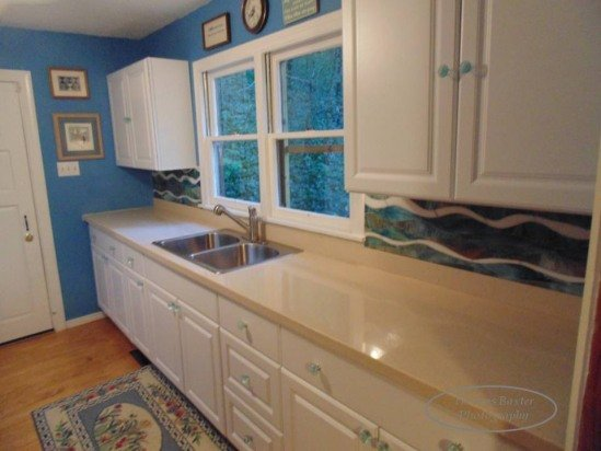 A custom-designed stained glass backsplash looks like the peaceful water that flows in the creek.