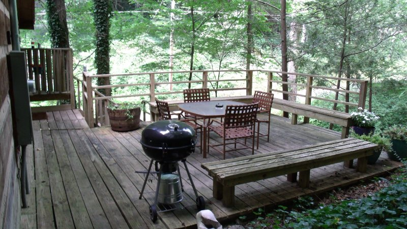 The spacious deck is surrounded by mature shade trees, laurel, and wildflowers.