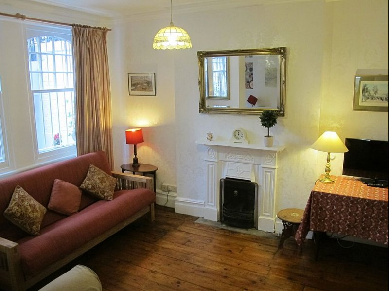 Comfortable sitting room with flat screen tv, working Victorian fireplace