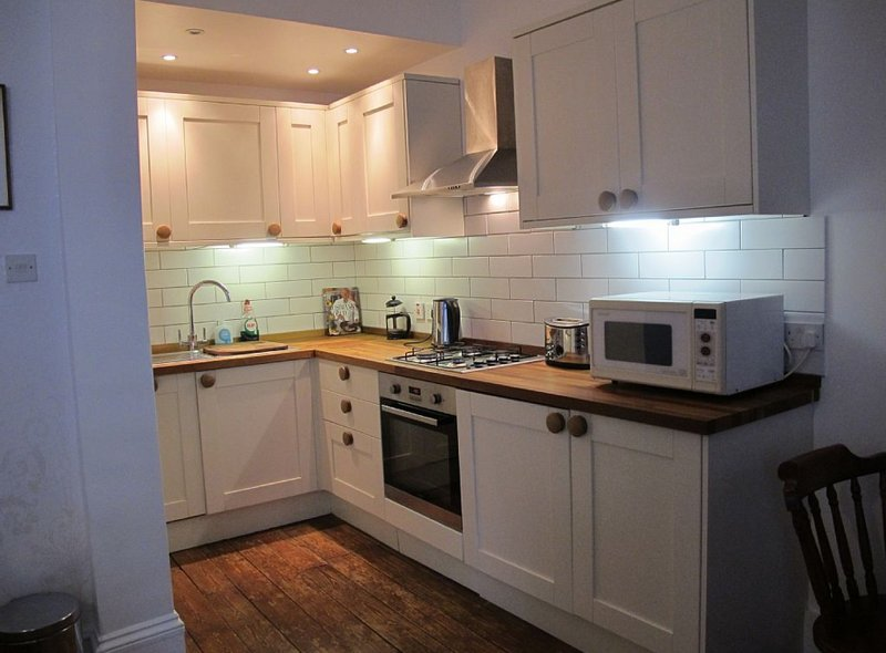 Tiled kitchen has washing machine, dishwasher, oven, microwave, toaster, kettle, cafetiere