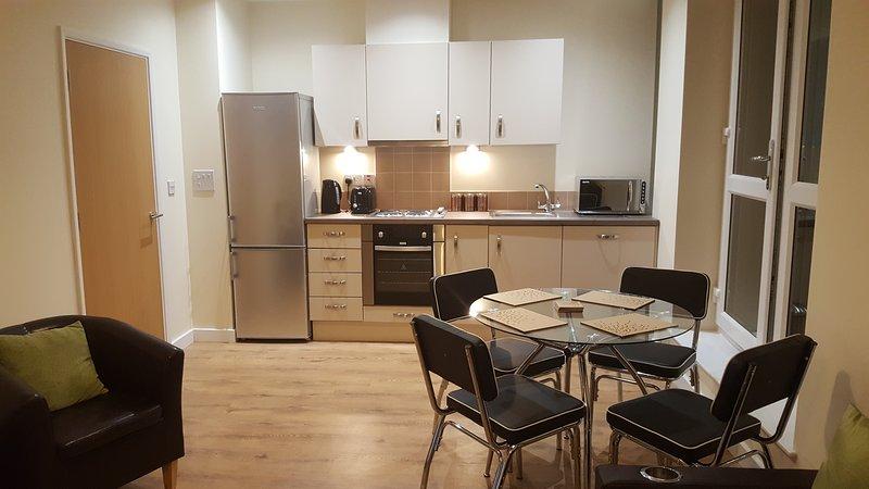 cozinha aberta, sala de jantar e sala de estar equipados com mobiliário elegante de luxo.
