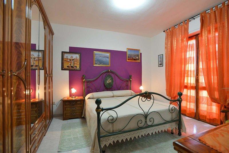 Maravilhoso quarto, quarto com varanda com vista para a rua, uma pequena mesa e cadeiras.