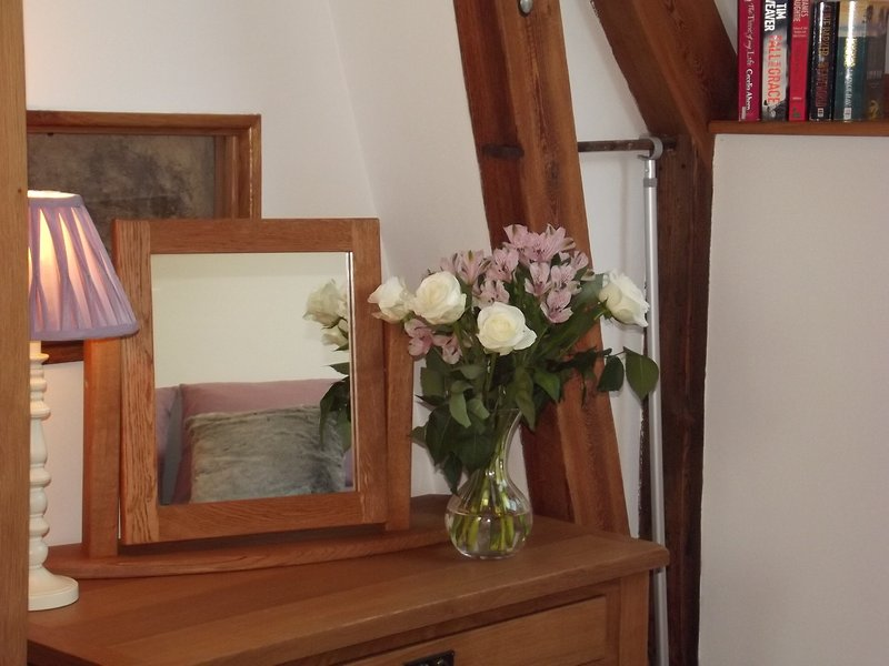 A piece of the original cob wall is framed behind glass at the back of the dressing table wall.