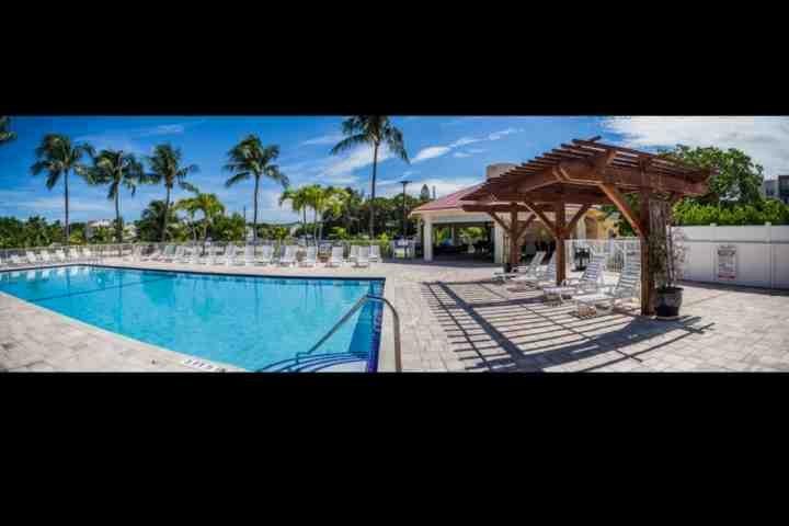 piscine et terrasse tropicale, avec des salons couverts de sièges et chaises pour votre utilisation.