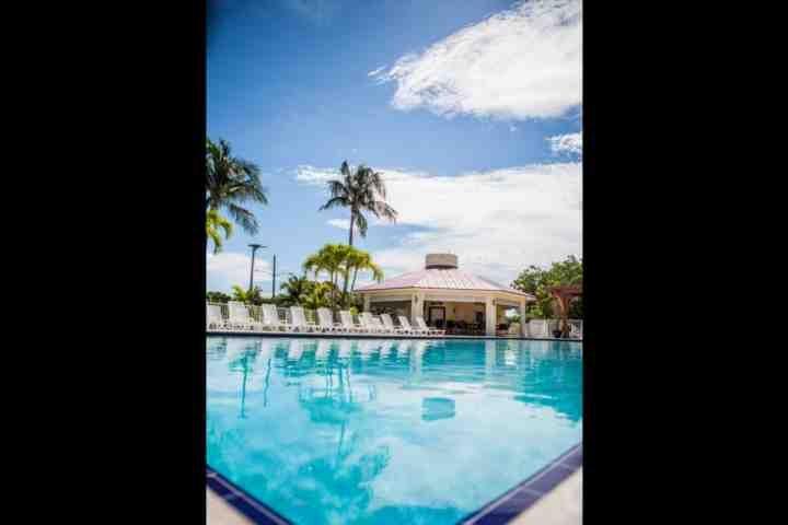 Ir para um mergulho e apanhar algum sol para fora em área de deck da piscina da comunidade e do sol.