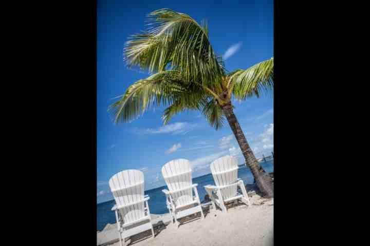 Apreciar a paisagem frente baía incrível da praia privada com cadeiras fornecidas para seu uso.