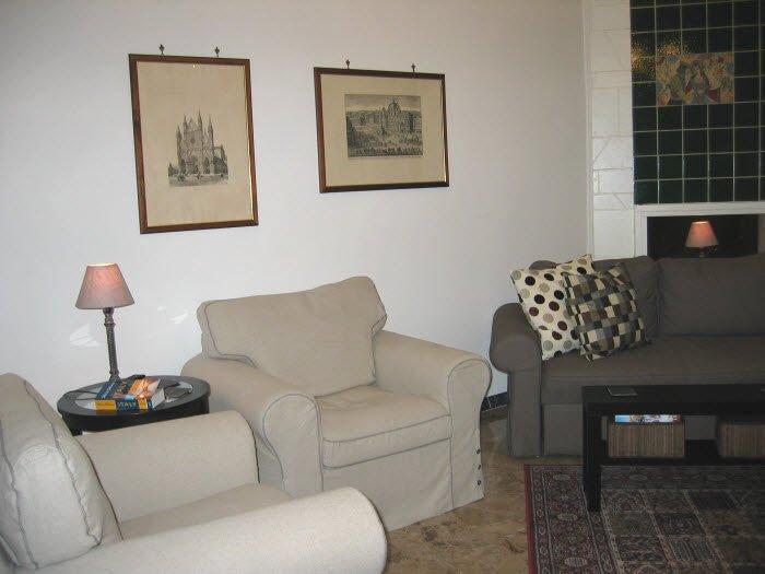 sala de estar tem duas cadeiras estofadas confortáveis e um grande sofá.