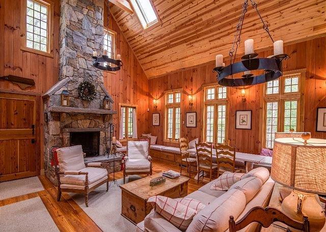Den with stone, wood burning fireplace.