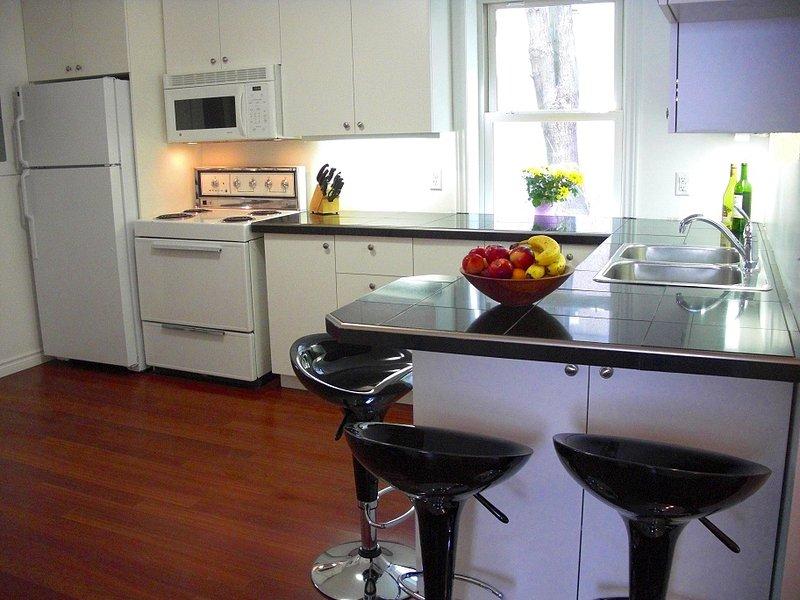 Aangepaste keuken met granieten werkbladen, barkrukken, twee koelkasten en veel kastruimte.