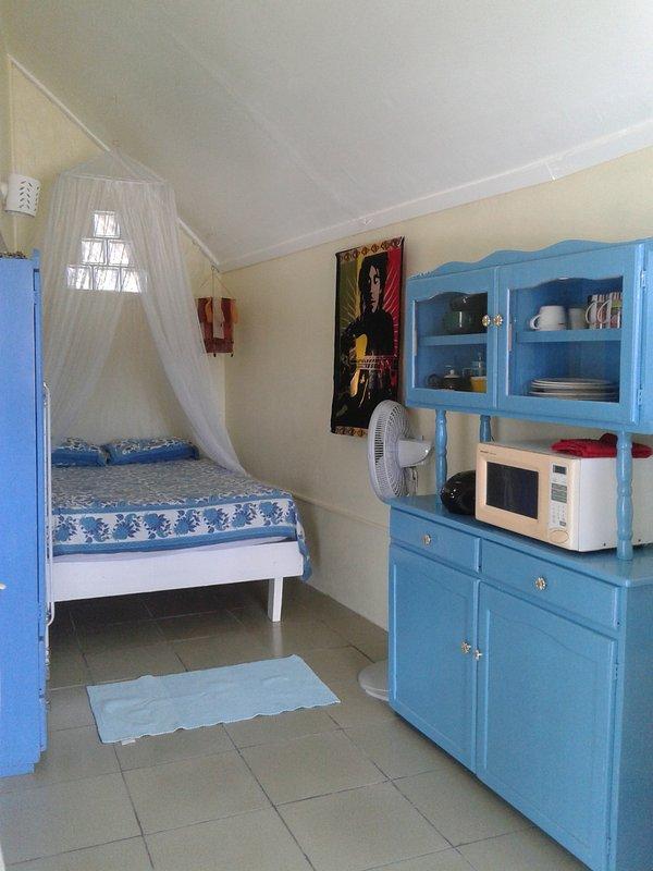 il letto matrimoniale e armadio, a bordo della tazza, radio e un forno a microonde