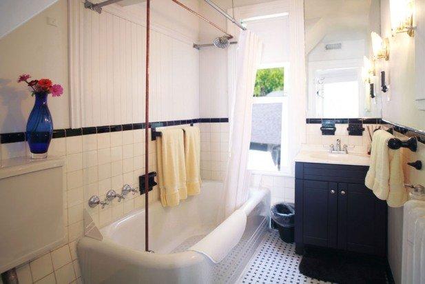 Questo bagno bianco e nero con una doccia / vasca è adiacente a 2 camere da letto al 2 ° piano