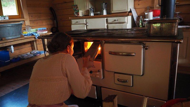 Le poêle à bois pour les amis dans une cuisine de cabane en bois rond, comme avant à grand-mère dans la Forêt Noire
