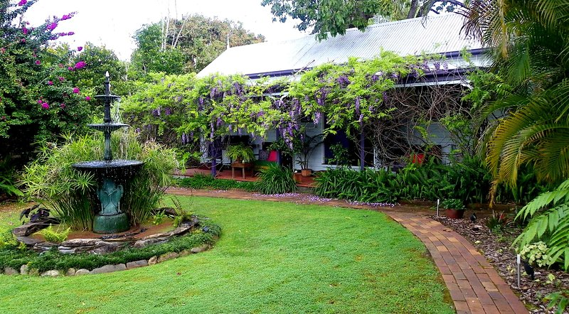 Wisteria cottage, pathway and fountain. On-site parking is at the rear of the property.