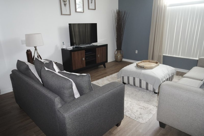 Gorgeous living room with all new composite, wood flooring. Nice TV with cable and Netflix too