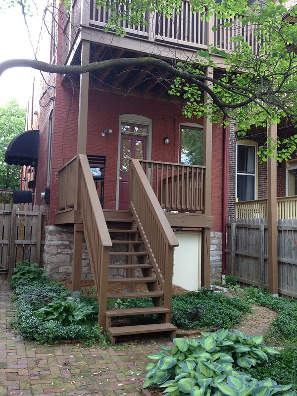 Back of house with fenced private backyard and first floor porch and second floor screened  porch.