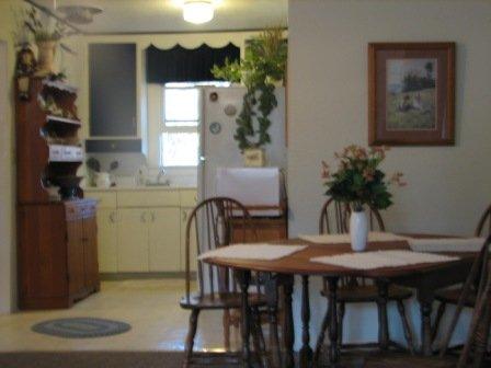 Cocina con elementos esenciales para el mantenimiento de la casa de luz que incluye microondas, tostadora y cafetera.