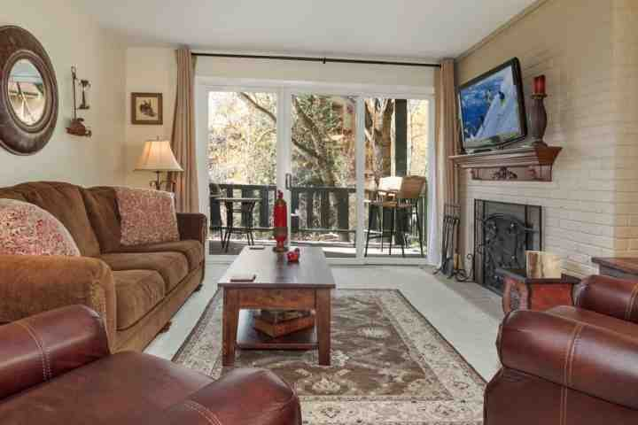Beautiful living room with flat screen TV, wood burning fireplace and deck access.  Deck is equipped with table and chairs and overlooks Gore Creek.