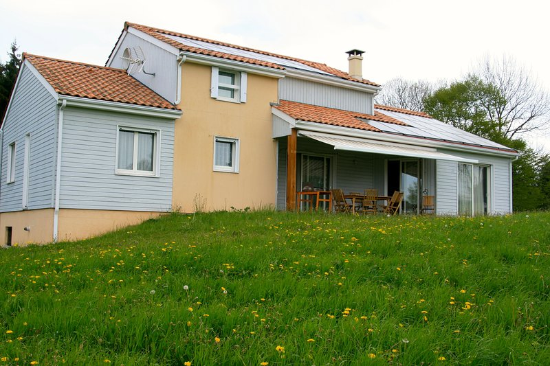 south facade on the meadow facing the volcanoes in the chain of Sancy and Puys with solar roof