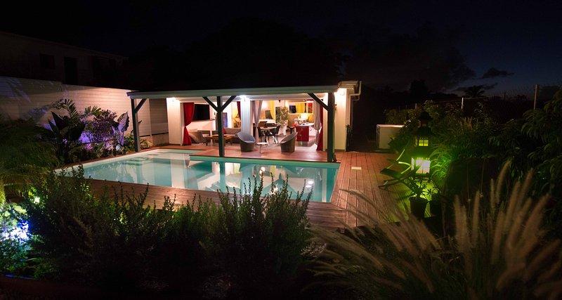 La villa de nuit avec la piscine et le jardin éclairés