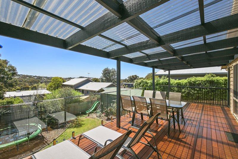 Zonovergoten terras, een panoramisch uitzicht, undercover, kijkt uit over de achtertuin. 8-seat tafel, ligstoelen