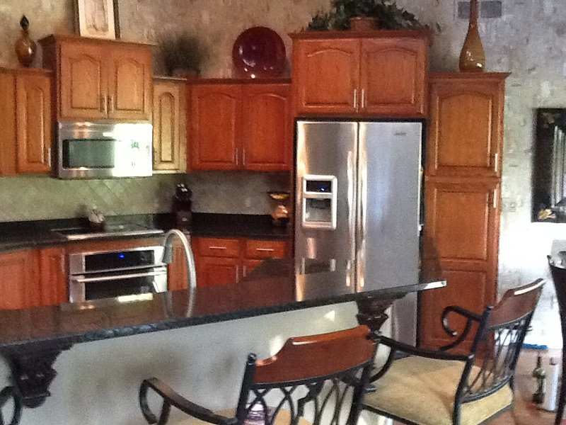 Open concept kitchen with seating of 4 at counter top bar and an additional 4 at kitchen table.