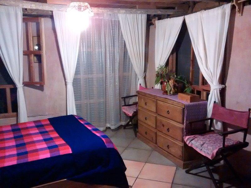 Room # 4 bei Casitas Kinsol Guest House in Puerto Morelos - Ein großes Zimmer mit einem Strohdach.