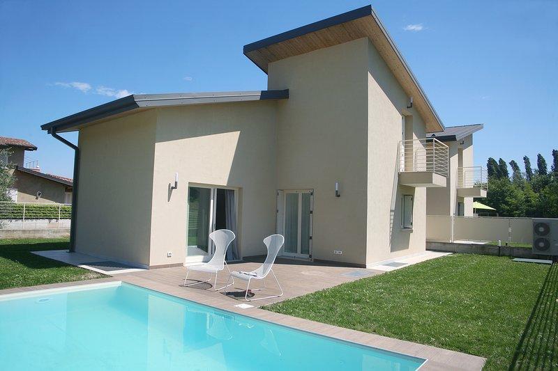 fachada exterior de la villa con vistas al patio, piscina y jardín