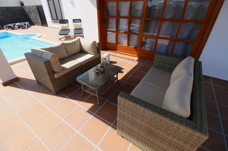 Rattan furniture underneath covered pergola