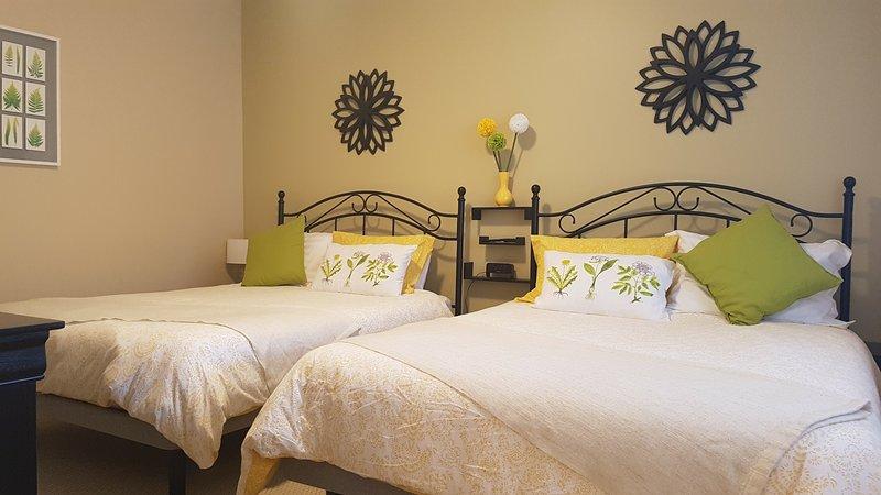 Bedroom 2 has 2 queen beds, nightstands for each and dresser.