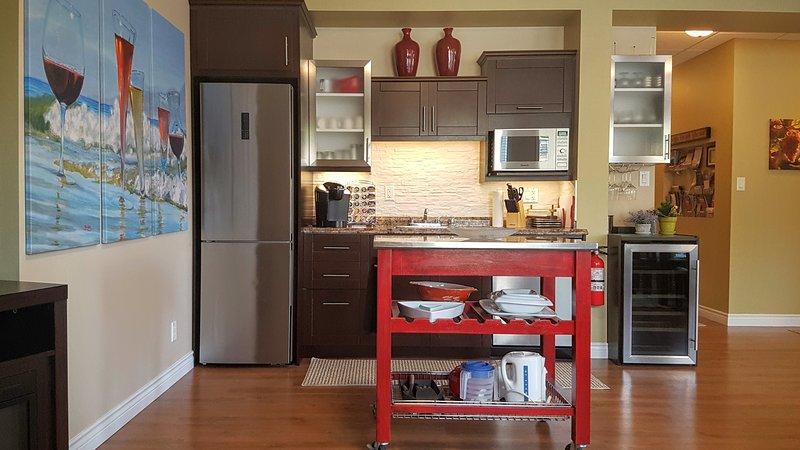 Barra de bebidas incluye una nevera grande, lavavajillas, microondas, fregadero y refrigerador de vino.