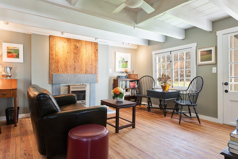 The living room features antique furniture and 200 year-old heart pine floors.