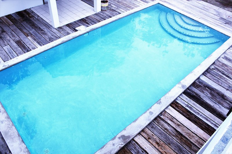 The brand new pool with a deck built with recovered wood.