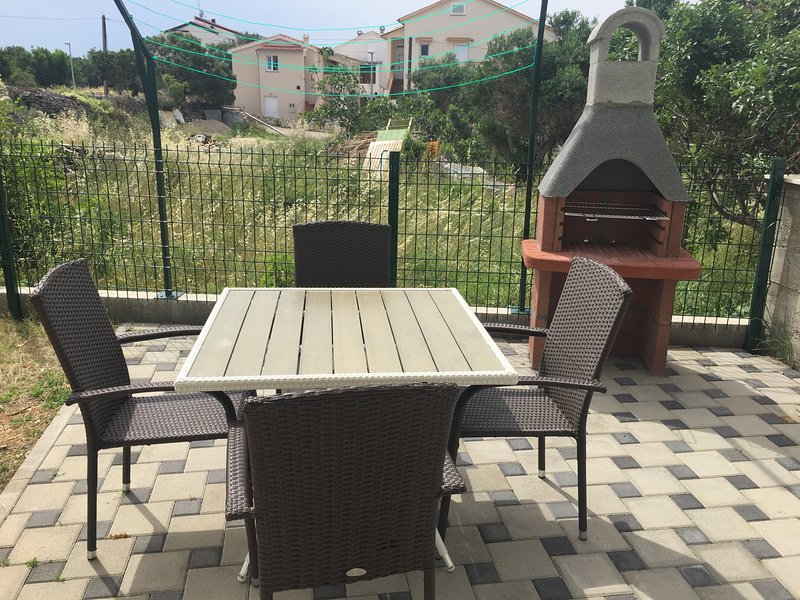 Terrace with table, chairs and barbecue.