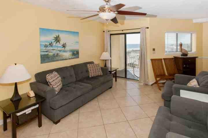 salon carrelé avec canapé, deux chaises latérales, deux tables d'extrémité et deux lampes