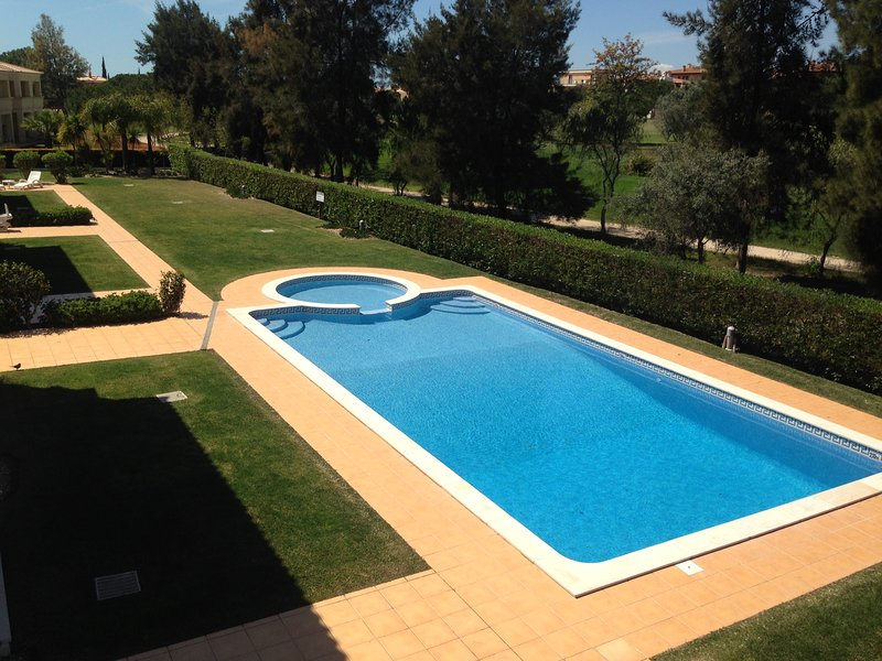 View of pool from balcony with BBQ table chairs and Sun loungers