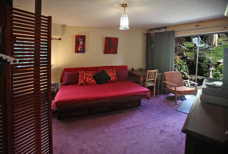 sala de televisión con entrada independiente al jardín. cama matrimonial con zumbido alimentación de aves fuera de la ventana