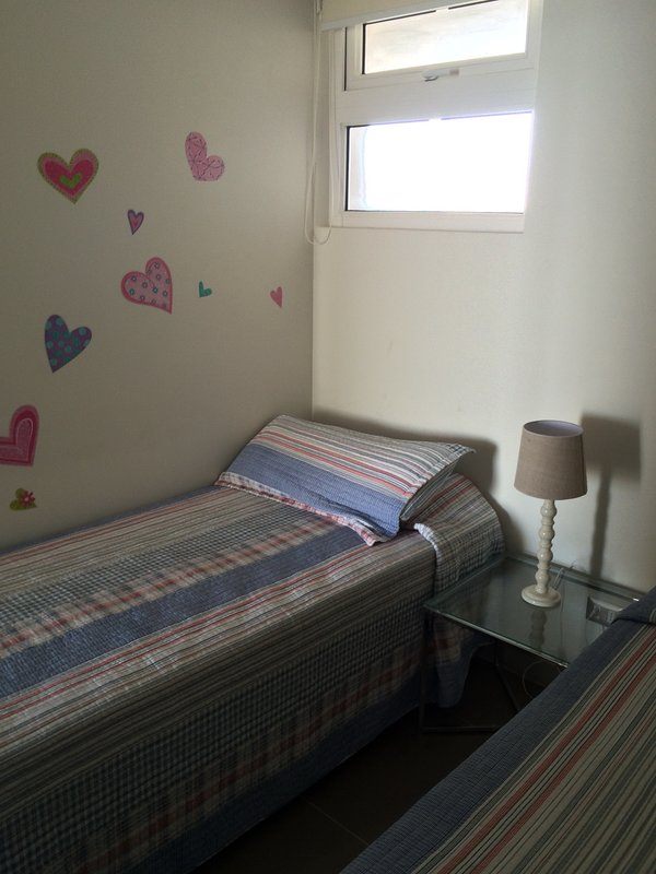 Additional room with 2 single beds and bedside table. Nursery decoration.