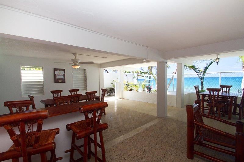 Patio privado frente a la playa cubierta con muebles de comedor