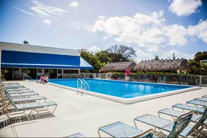 Tropical pool with chaise lounges and tiki huts by the clubhouse with tables and chairs indoors