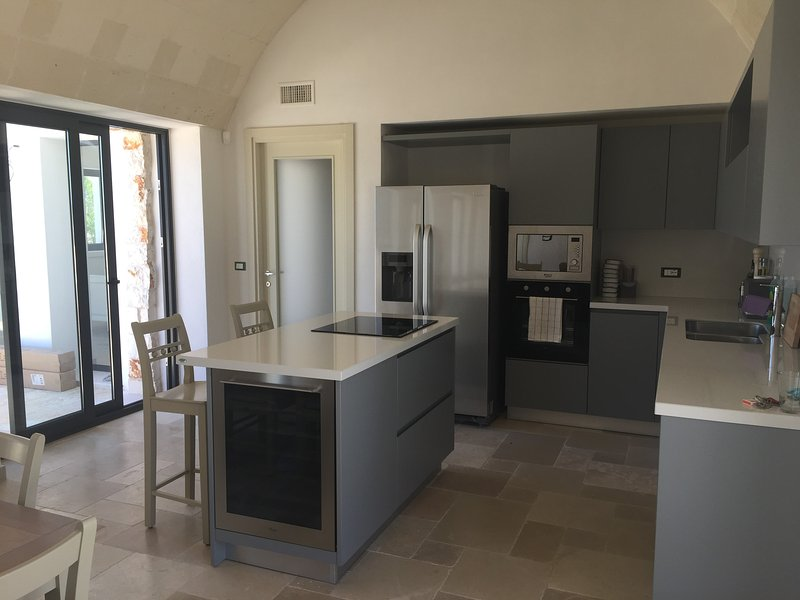 Open plan kitchen with wine fridge, fridge/freezer, microwave, dishwasher, oven and ice maker