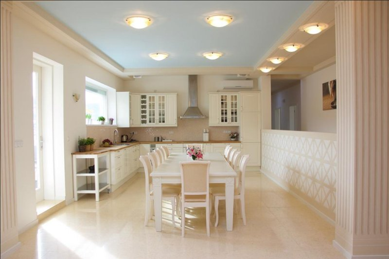 Modern fitted kitchen with a table for ten people.