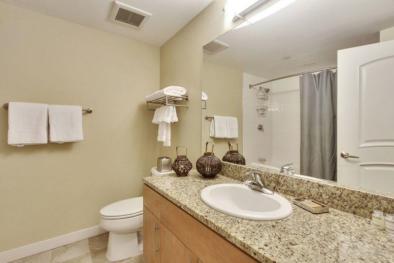 Baño completo para huéspedes con encimeras de granito, ropa de cama incluida