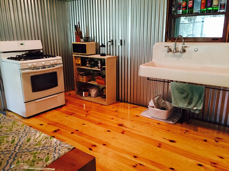 Farm sink, full sized stove and side by side fridge in the kitchen.