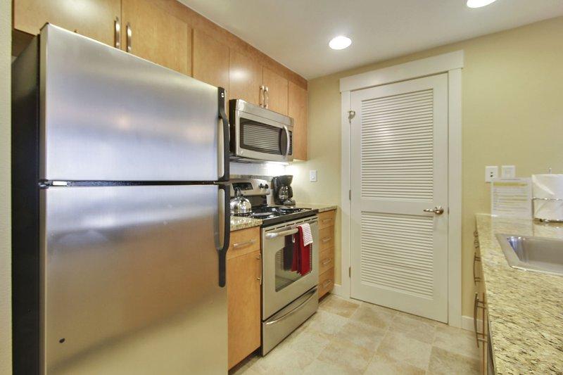 Cocina completa con encimeras de granito y electrodomésticos de acero inoxidable